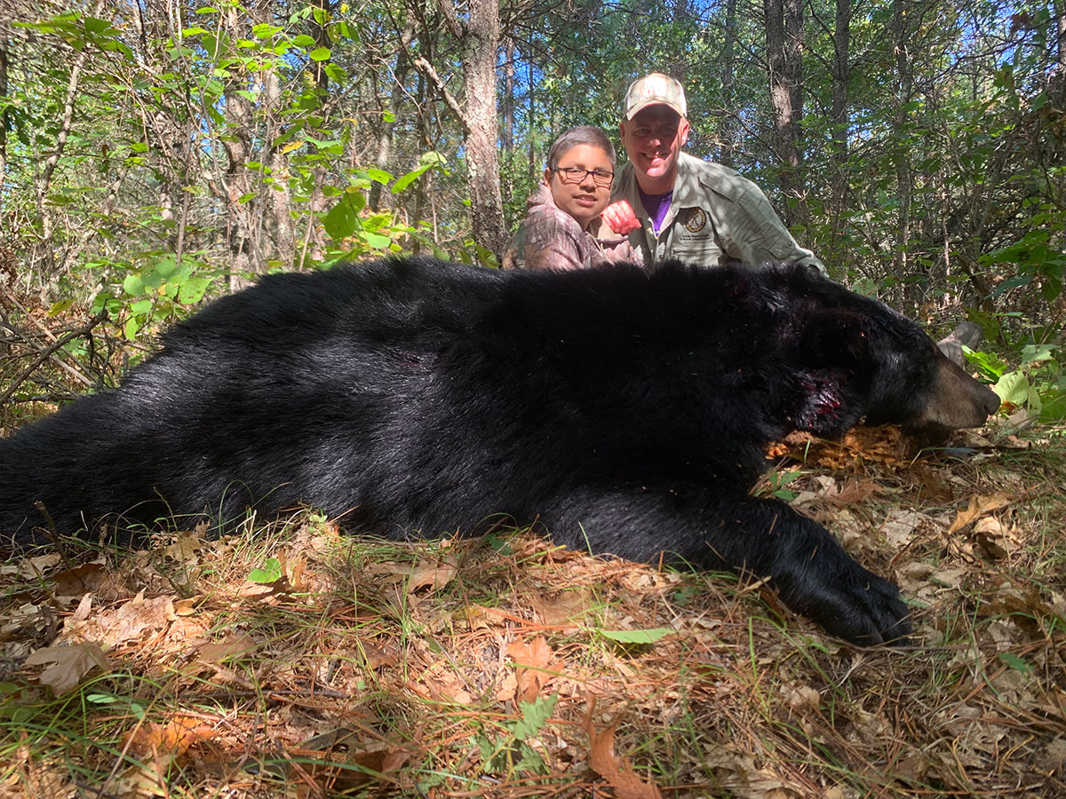 Young hunter with black bear